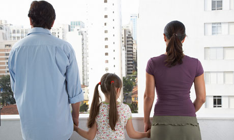 Parents and daughter (8-10) holding hands on balcony, rear view