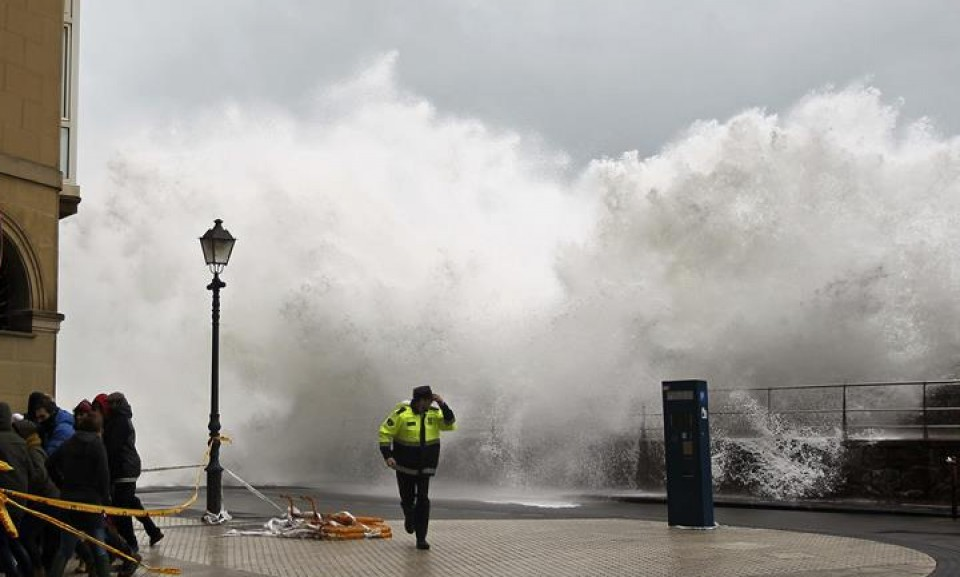 Una ola alcanza a un municipal en el Paseo Salamanca. Foto: EFE